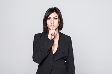 Hush. Businesswoman with finger on her lips gesturing for quiet isolated on gray background