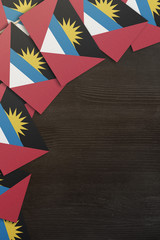 Antigua and Barbuda small flags framing a wood texture background with copy space