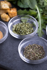 Glass ingredient dishes of dried thyme and parsley seasoning