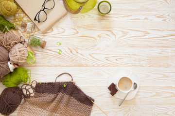 A woman knits a white and broun knitted fabric of woolen yarn. Knitting needles. Aged background. Green and white.