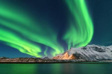 Tuinposter Noorderlicht Aurora borealis. Lofoten islands, Norway. Aurora. Green northern lights. Starry sky with polar lights. Night winter landscape with aurora, sea with sky reflection and snowy mountains. Nature. Travel