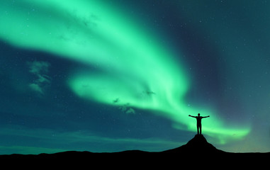 Aurora and silhouette of standing man with raised up arms on the mountain in Norway. Aurora borealis and happy man. Starry sky, green polar lights. Night landscape. Northern lights. Travel and tourism