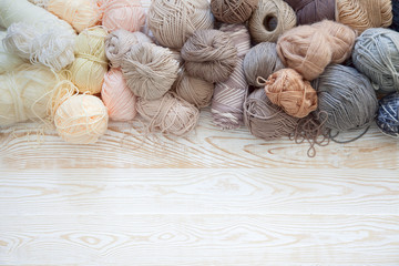Wool and cotton yarn for knitting of neutral natural color. Background is aged white wood.