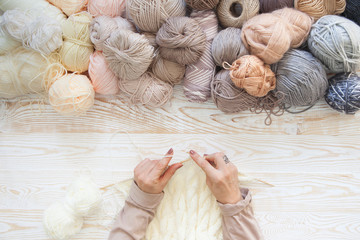 Wool and cotton yarn for knitting of neutral natural color. The woman knits knitting.