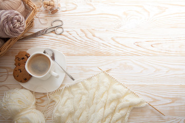 Wool and cotton yarn for knitting of neutral natural color. The woman knits knitting. A cup of black coffee.