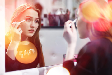 A young girl does make-up in a beauty salon. The girl in front o