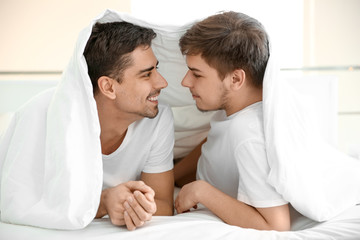 Young gay couple lying under blanket on bed in light room