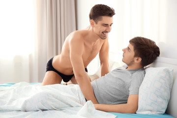 Young gay couple together on bed in light room