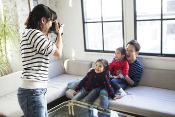 お父さんと子供たちの写真を撮っている、母。