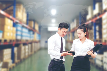 Asian Business man and Business woman worker in warehouse using tablet checking boxes Logistic import and export concept