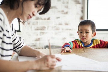 お母さんが紙にメモを書いている。男の子が見ている。