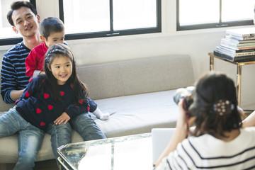 お父さんと子供たちが、お母さんに写真を撮ってもらっています。