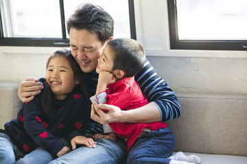 お父さんと子供たちが楽しそうに寄り添っている。