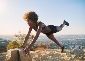 athletic young african american woman doing stretches and pushups at runyon canyon with view of los angeles in background