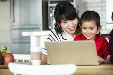 お母さんと男の子が一緒にノートパソコンを見ている。