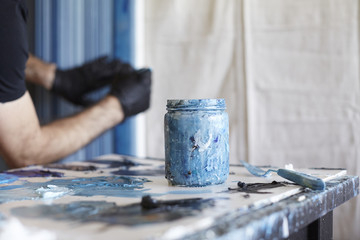 Close up of paint jar with man painting in the background