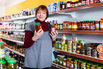 female buyer choosing canned jar of tomato paste at the supermarket