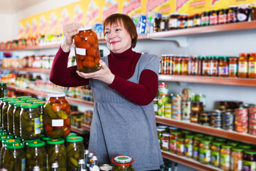 female consumer holding glass jar of tomatoes