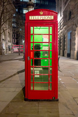 Red royal telephone booth in London city night scene