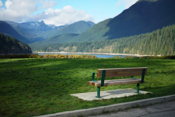 Empty park bench in front of lake and mountains