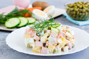 Traditional Russian salad olivier on a plate and ingredients for its preparation