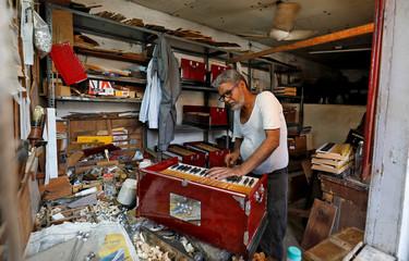 A craftsman prepares a harmonium at a musical instruments shop in the old quarters of Delhi