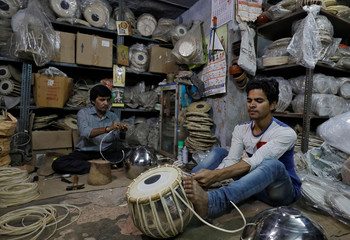 "Craftsmen prepare ""duggi"", an Indian percussion instrument, at a musical instruments shop in the old quarters of Delhi"