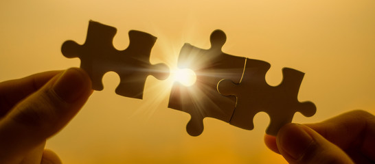 Silhouette Woman hands connecting couple puzzle piece against sunrise effect, businesswoman holding jigsaw with sunset background. Business solutions, target, success, goals and strategy concepts Wall mural