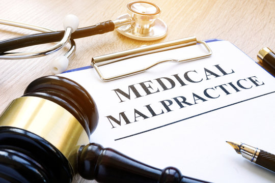 Clipboard with documents about medical malpractice and gavel.