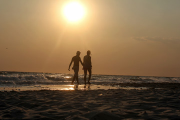 Young couple is walking in the water on summer beach. Sunset over the sea.Two silhouettes against the sun. Man and woman in holiday honeymoon trip.