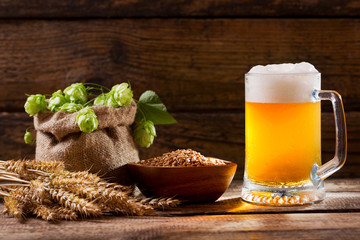 Mug of beer with green hops, wheat ears and grains