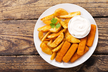 plate of fish sticks with fried potatoes on a wooden table