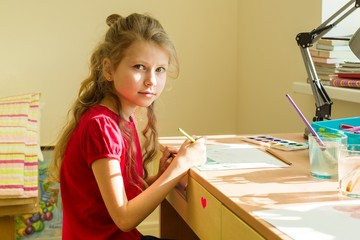 Adorable girl 7 years old, draws watercolor at the table at home. Child creativity, recreation, development