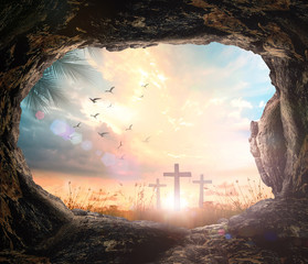 Resurrection of Easter Sunday concept: Empty tomb stone with three cross on meadow sunrise background