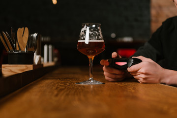 glass of fresh cold beer and person playing with joystick behind in pub
