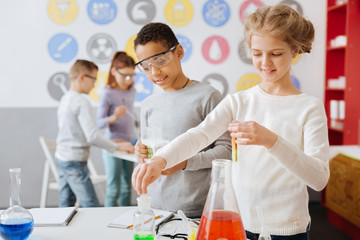 Interesting chemistry. Charming teenage girl holding a test tube with a chemical and taking some milliliters of another from a flask while conducting a chemical experiment with her classmate