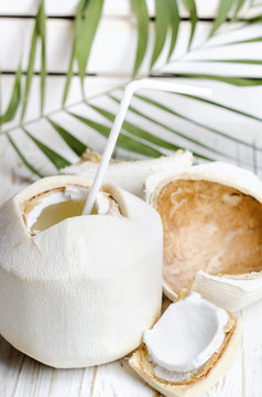 Young coconut on white wooden background.