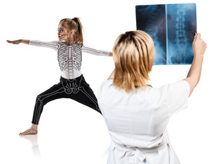 Female doctor looks on x-ray of little girl in yoga pose.