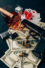 Gambling concept with gun, whiskey and money on casino table with cards and dice