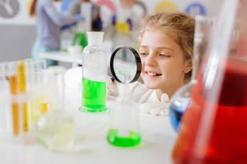 Helpful device. Cute pretty teenage girl squatting near the table in the chemical laboratory and checking for sediment in the flask with the help of a magnifying glass