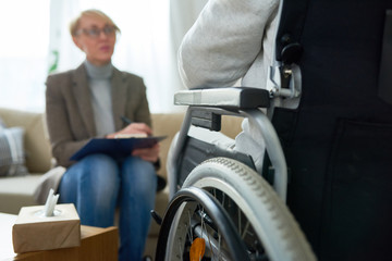 Portrait of  female psychiatrist interviewing handicapped  man during therapy session, copy space