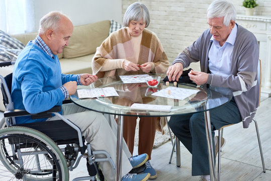 Group of senior people playing lotto game sitting at glass table in living room