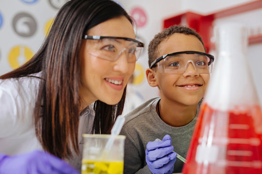 Everything goes well. Beautiful young chemistry teacher and her upbeat male student watching a chemical reaction and smiling, being satisfied with the reaction