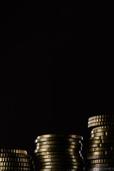 close up view of stacks of coins isolated on black