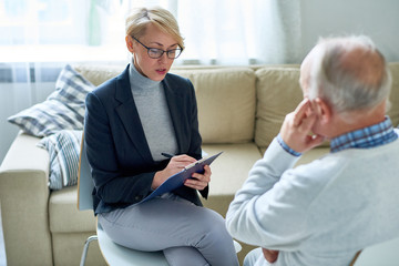 Portrait of blonde female psychologist talking to senior man during consultation, copy space