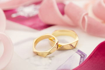 Golden wedding rings on pastel background with pink ribbons
