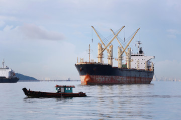 Small passenger boat running in the sea and have cargo ship.