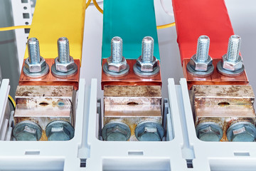 The electric busbars are connected to the automatic switches by a bolted connection. Busbars are installed in an electric Cabinet. Busbars labeled red, green and yellow. Front view.
