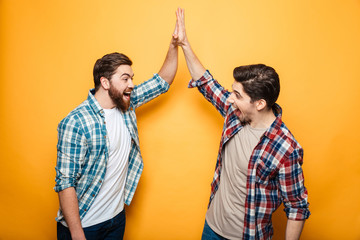 Portrait of a two happy young men giving high five