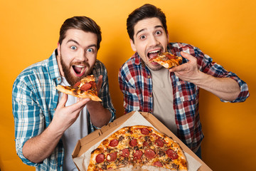 Cadres-photo bureau Pizzeria Portrait of a two hungry young men eating pizza